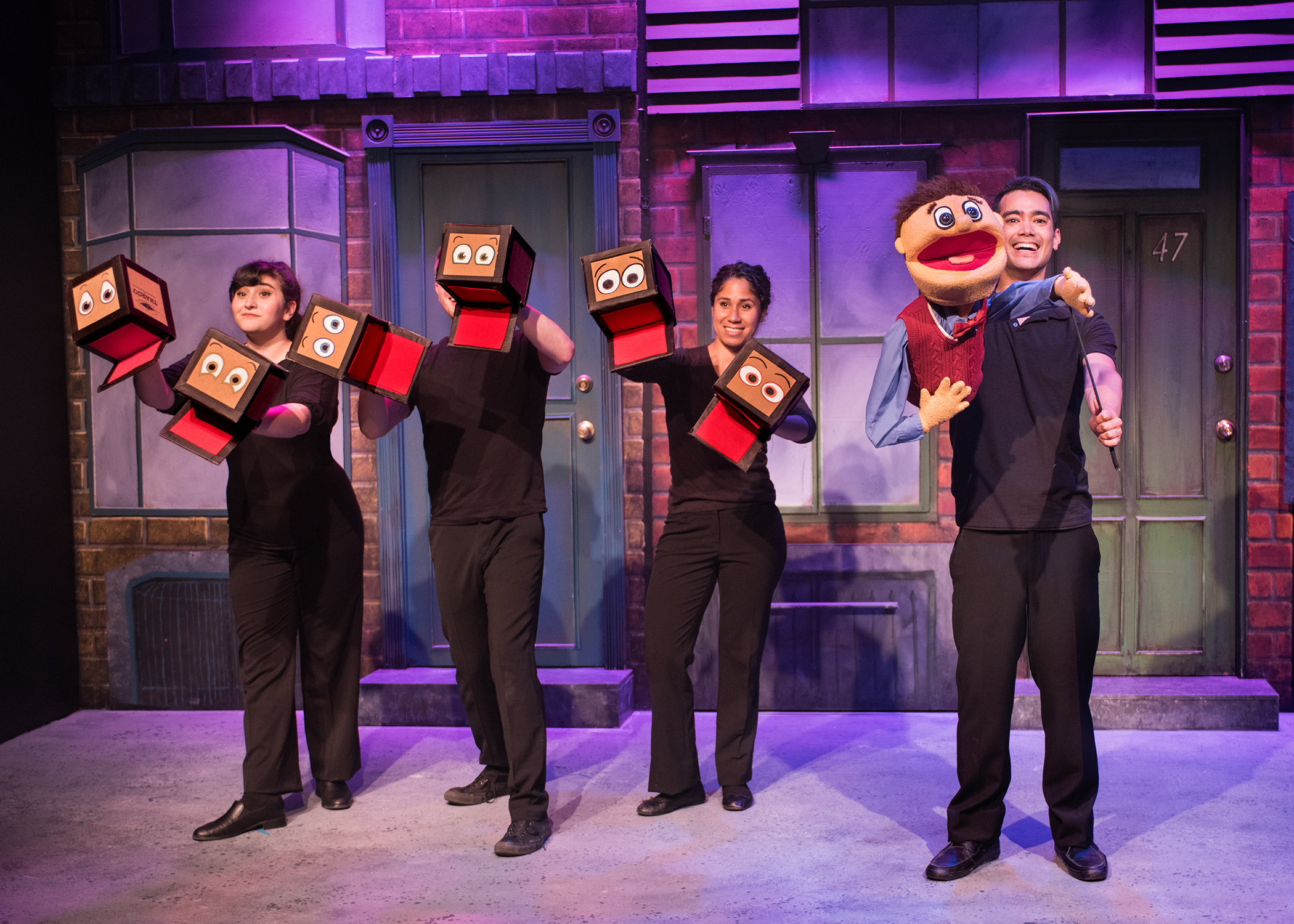 L to R: The Moving Boxes (Maya Michal Sherer, Jake Gale and Alex Akin) and Princeton (Nick Rodrigues) move into Avenue Q. Photo by Lois Tema.