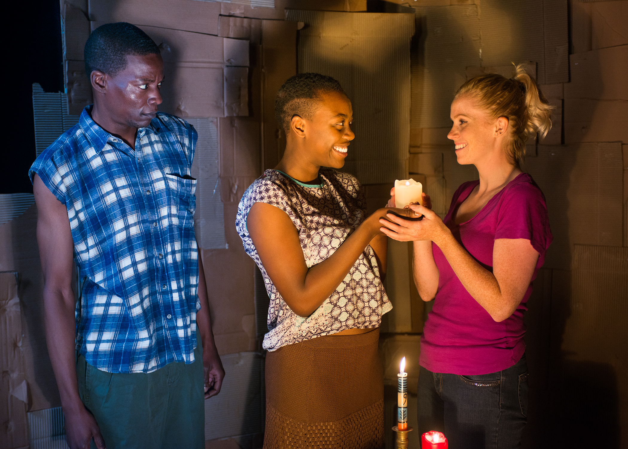 R to L: Child-soldier, Pika (Howard Johnson) looks on as Adiel (Gabriella Momah) and Chris (Megan Timpane) share a stolen moment. Photo by Lois Tema.