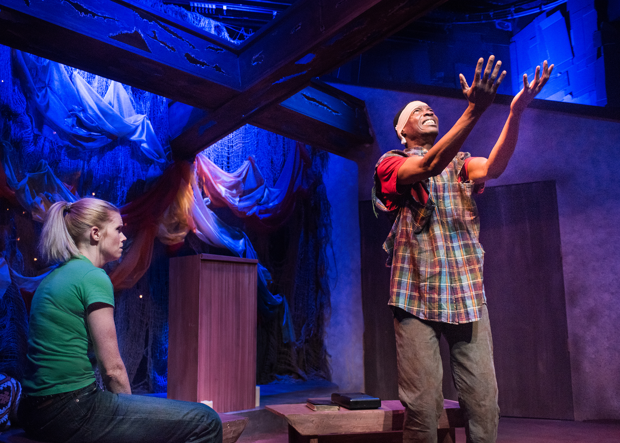 Chris (Megan Timpane) listens as Pika (Howard Johnson) recounts the horrors of war he has seen. Photo by Lois Tema.
