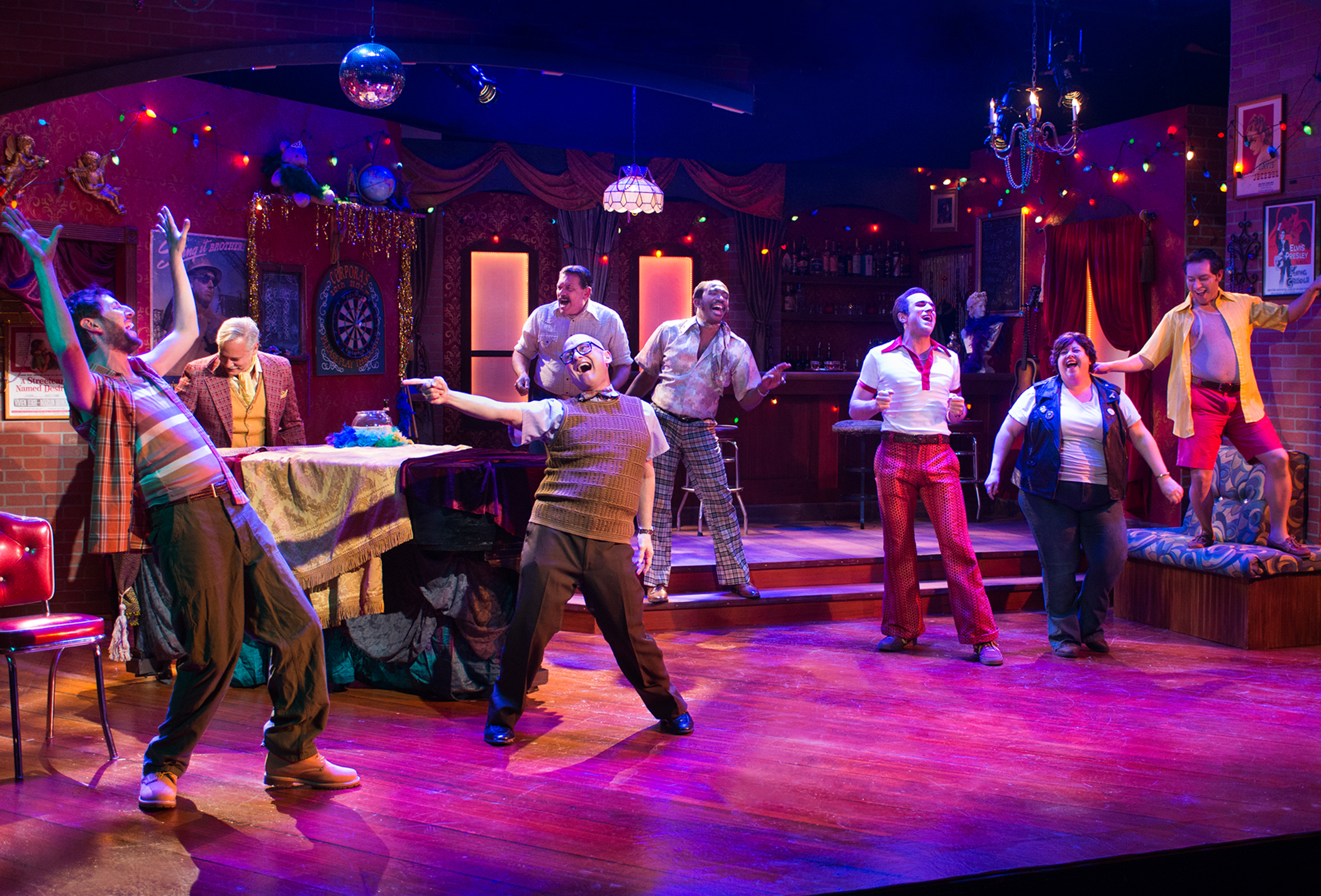 Pictured L to R: The regulars of the UpStairs Lounge (Chris Morrell, Cameron Weston, David Bicha, Gary M. Giurbino, Anthony Rollins-Mullens*, Coleton Schmitto, Jessica Coker, and Jesse Cortez) live in their own kind of paradise. Photo by Lois Tema. *Appears courtesy of Actor's Equity Association, the Union of Professional Actors and Stage Managers in the U.S.